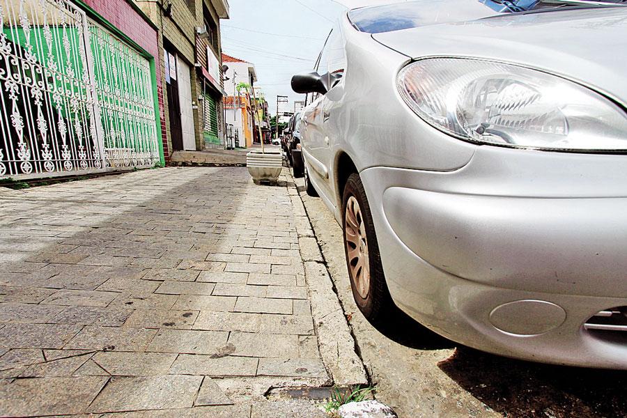 É comum encontrar carros estacionados em frente a guias rebaixadas pelo bairro