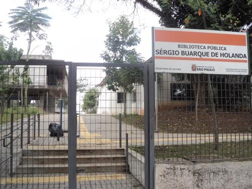 Entrada para prédio improvisado, que deveria ser acessível, está fechada com cadeado em portões
