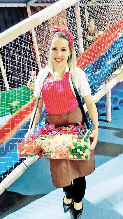 Promotora da PR Gourmet com o bar de guloseimas durante festa