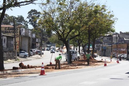 Homens trabalham na recolocação de terra no canteiro central da Avenida Itaquera